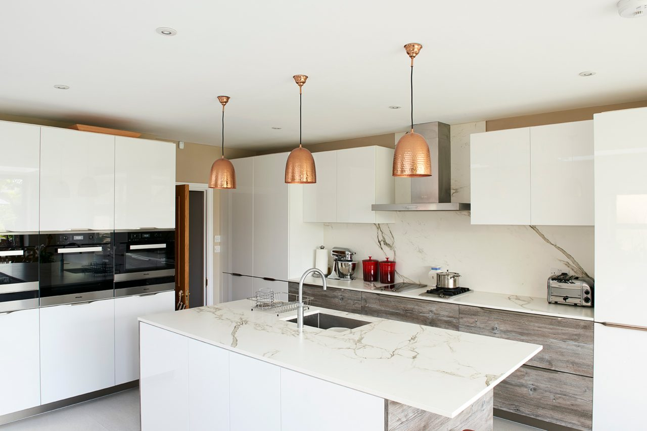 Refurbished kitchen with cooper pendants and marble worktop and splash back