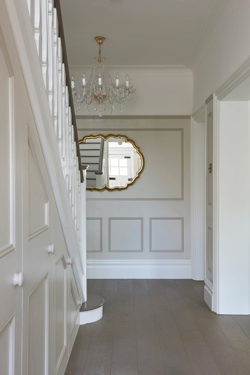 A grand entrance hall with chandelier and mirror