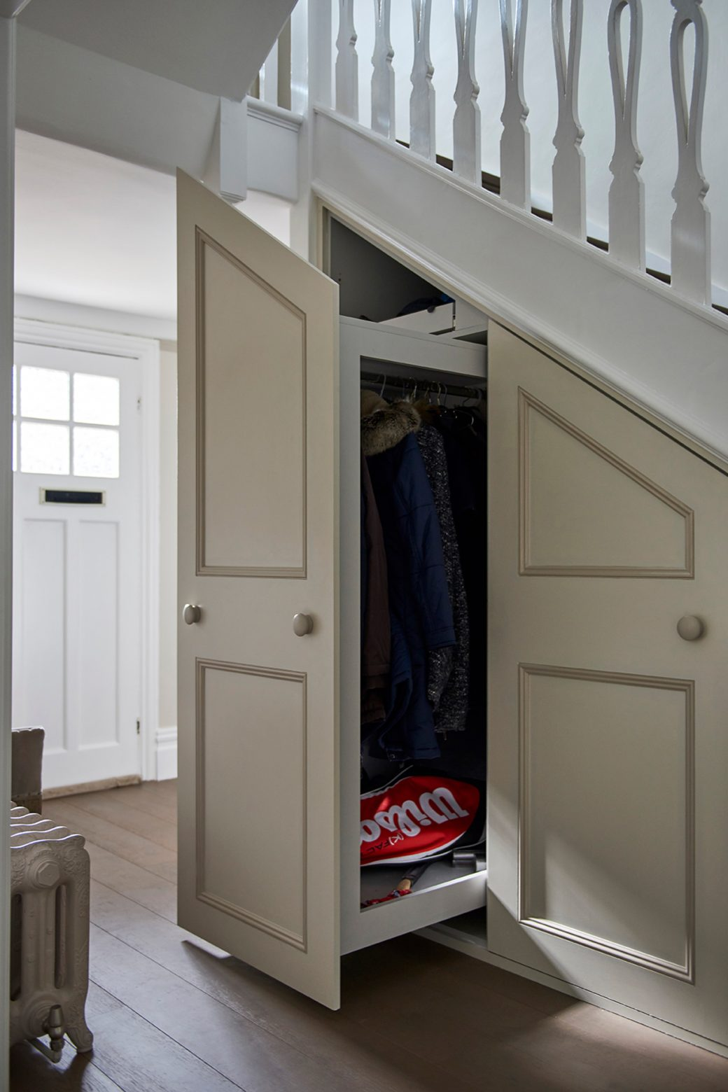The built in storage opened to show the under stairs system