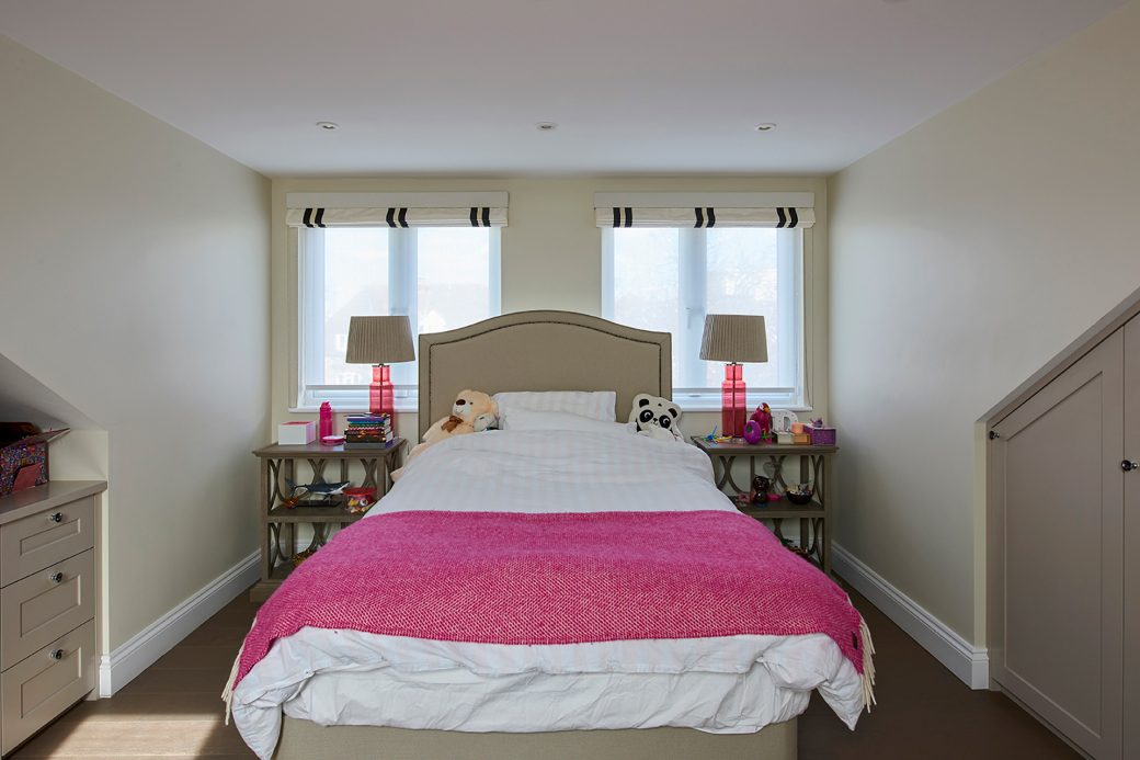 Child's bed with pink throw