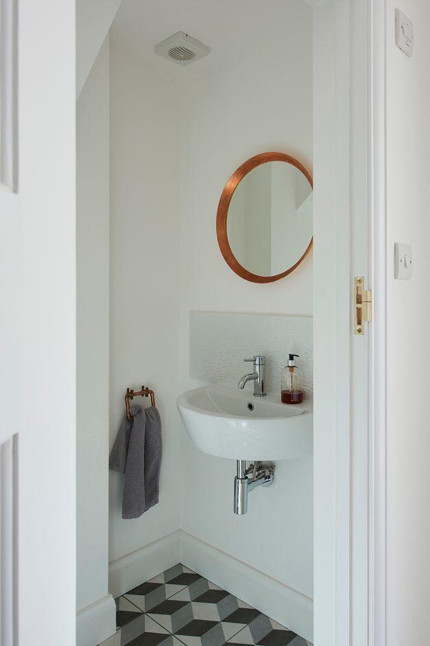 Copper mirror in contemporary white bathroom