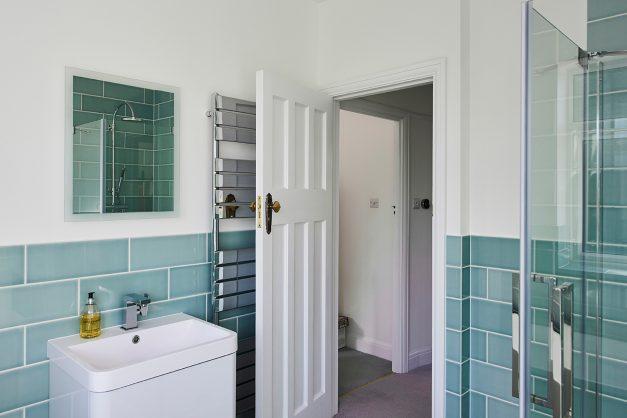 1930's door and azure blue tiles in bathroom