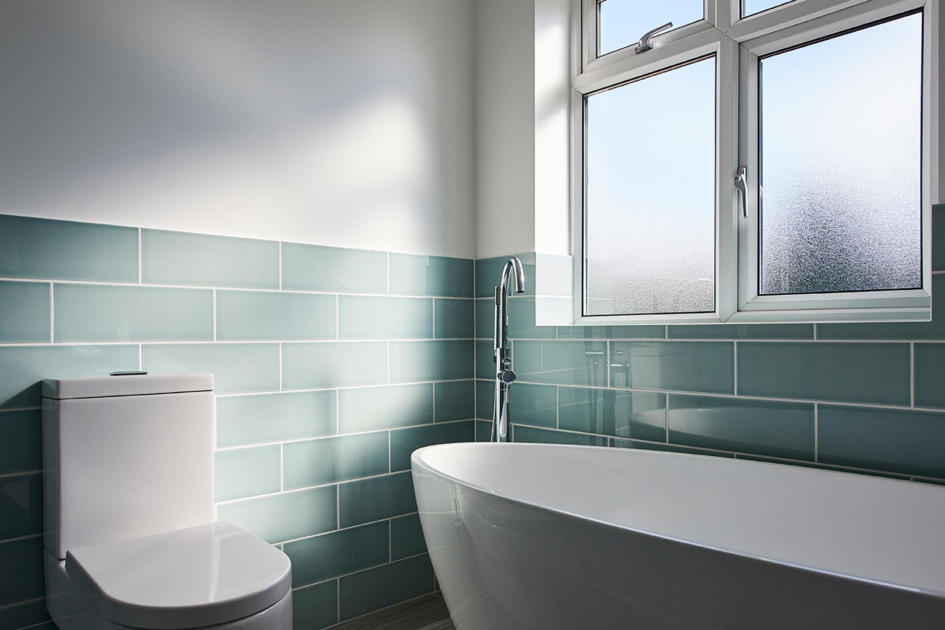 Azure blue tiles next to white free standing bath