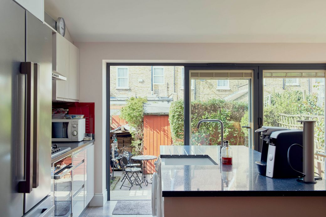 The new kitchen looks out onto the patio through bi-folding doors