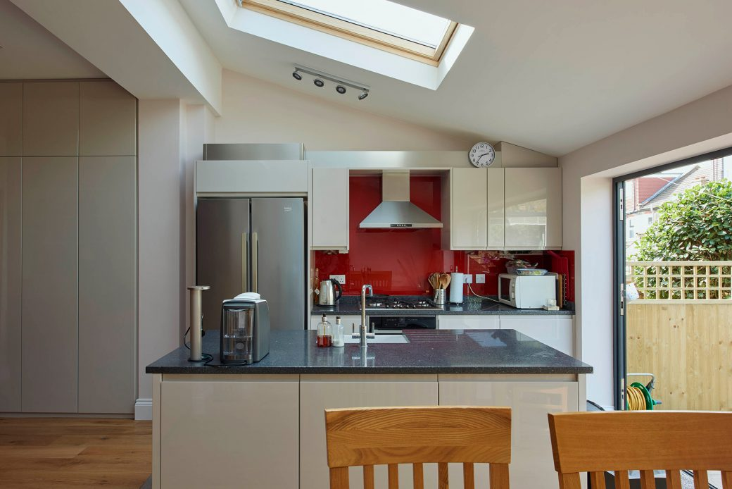 Off white kitchen cupboards with a bright red splash back