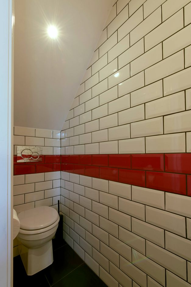 Bathroom with white subway tiles with a contrasting red stripe of tiles
