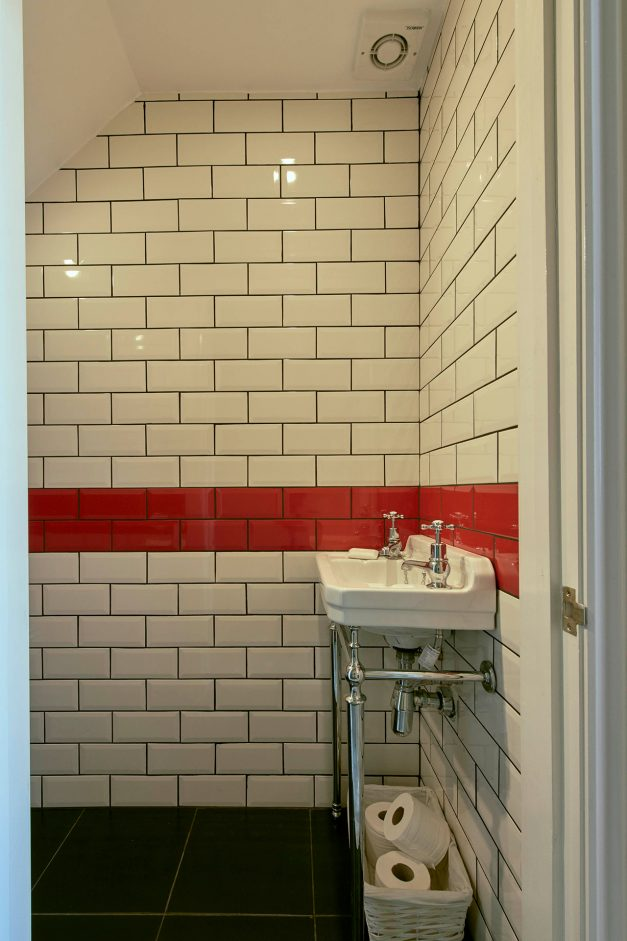White and red subway tiles decorate this bathroom